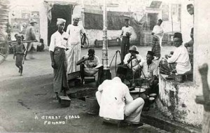 'A Street Stall, Penang' shows customers enjoying Mamak food at a street junction. Nasi kandar, gandum and other 'mamak' food used to be sold by itinerant hawkers carrying their food in baskets suspended from shoulder yokes (kandar). Wade Collection.