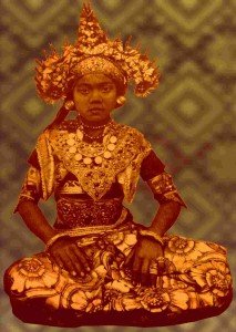 A young Balinese dancer, early 20th century, wearing a gold crown embellished with fresh flowers, with armlets of a traditional Balinese design with Garuda motifs.